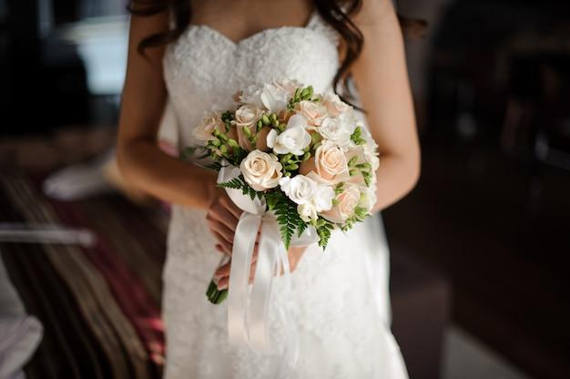 Retrato de novia en vestido de novia largo lujoso blanco, velo y ramo