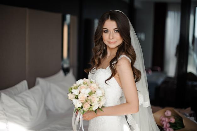 Retrato de novia en vestido de novia, velo y ramo con rosas y helechos