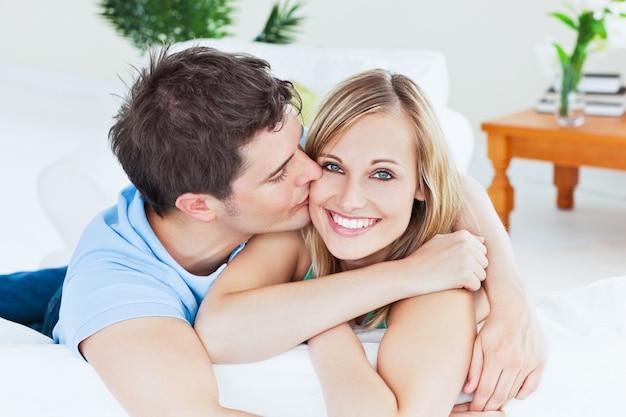 Retrato de un novio atento besando a su novia sonriente relajante en la sala de estar