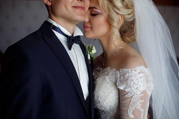 Retrato de novios de cerca. retrato de un amoroso recién casados. la novia abraza suavemente y besa al novio. día de la boda. retrató una feliz pareja de enamorados en el interior