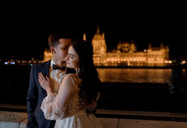 Retrato de novios con hermosa vista de la ciudad de noche, boda luna de miel en la arquitectura europea