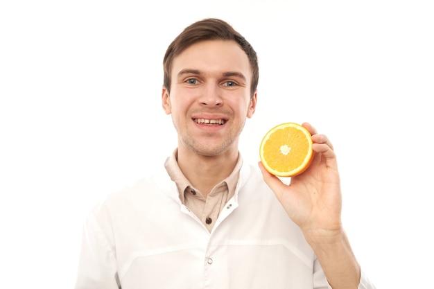 Retrato de un nutricionista médico masculino sonriente positivo con naranjas. coma vitamina c, manténgase saludable, alimentos dietéticos en concepto de temporada de resfriados y gripe