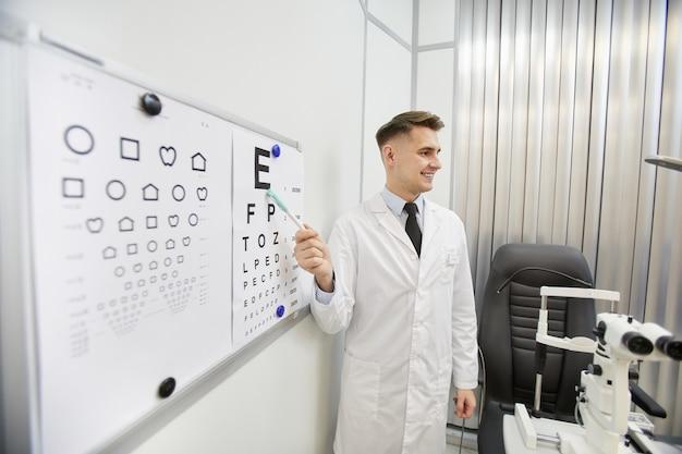 Retrato del oftalmólogo joven sonriente apuntando a la tabla de visión