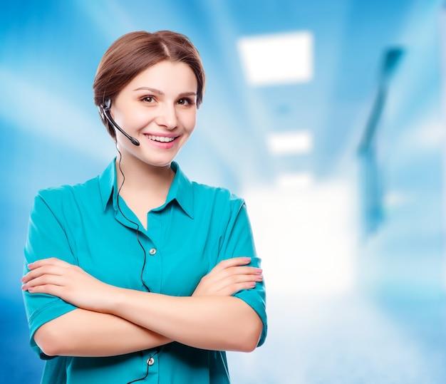 Retrato del operador joven alegre sonriente feliz del teléfono de la ayuda