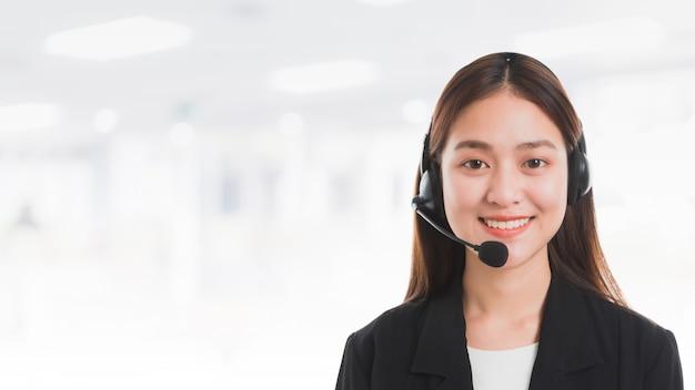 Retrato del operador sonriente hermoso asiático del teléfono de la atención al cliente de la mujer en fondo de la bandera del espacio de oficina.