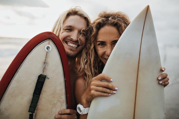Retrato de optimista chico y chica escondidos detrás de tablas de surf