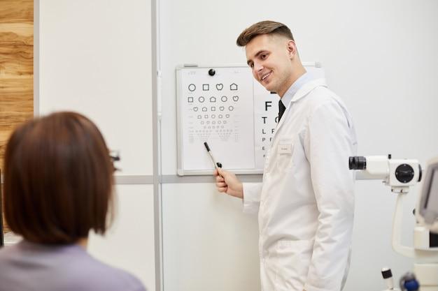 Retrato del optometrista joven sonriente apuntando a la tabla de visión