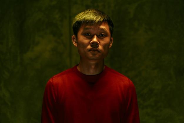 Retrato oscuro triste y cansado del hombre asiático