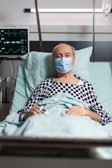Retrato de paciente anciano enfermo con mascarilla quirúrgica descansando en la cama de un hospital, con goteo intravenoso adjunto en la mano con oxímetro conectado en el dedo