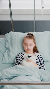 Retrato de paciente hospitalizado niña enferma sosteniendo oso de peluche descansando en la cama durante la co ...