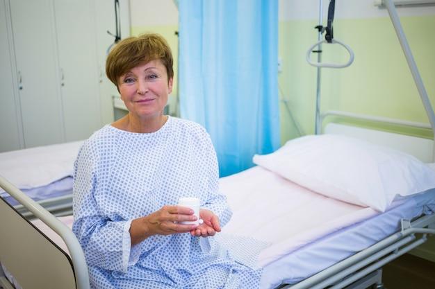 Retrato de paciente senior sentado en una cama con medicina