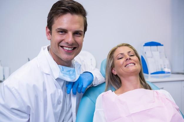 Retrato de paciente sonriente y dentista sentado en una silla
