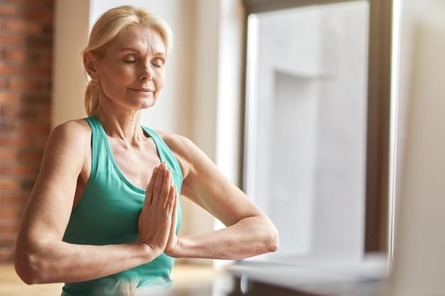 Retrato de pacífica mujer rubia madura practicando yoga meditando con los ojos cerrados en casa en el