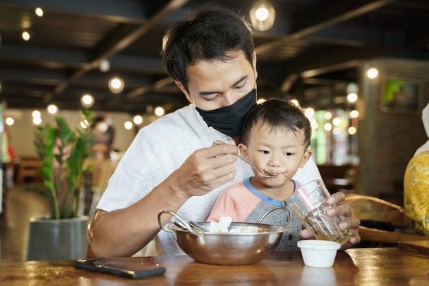Retrato de padre asiático alimentando a su hijo en el restaurante