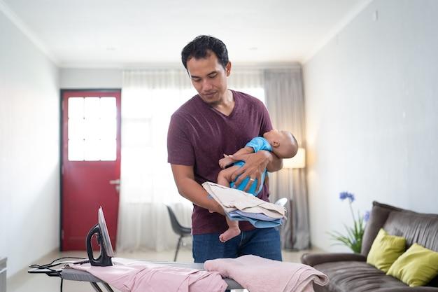 Retrato de padre asiático planchando su ropa mientras sostiene a su bebé en su mano