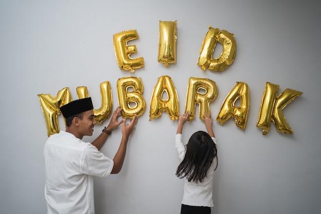 Retrato, padre e hija, musulmán, decoración, eid mubarak, carta, hecho, de, globo, decoración, contra, la pared, en casa