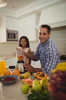Retrato de padre e hija preparando batidos en cocina