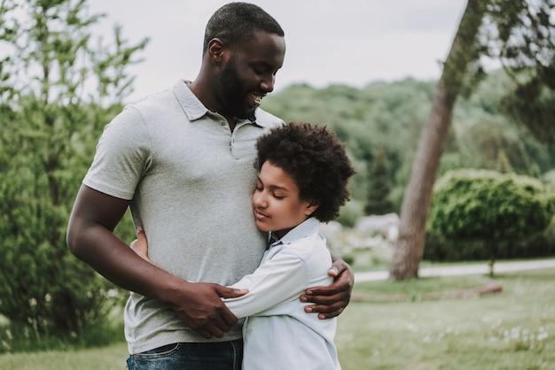 Retrato de padre e hijo se abrazan en la naturaleza.