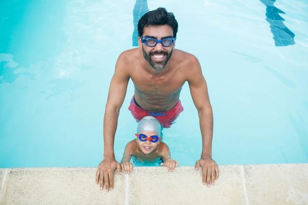 Retrato de padre e hijo con gafas de natación en la piscina