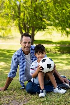 Retrato de padre e hijo sentados en el parque