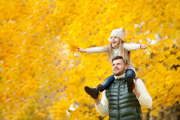 Retrato del padre feliz que detiene a su hija en hombros, con las hojas en handson el parque del otoño