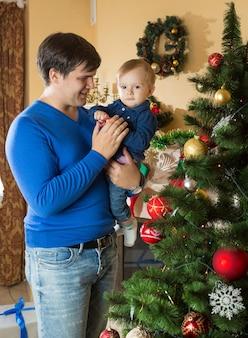 Retrato de padre joven feliz abrazando a su hijo de 1 año cerca del árbol de navidad