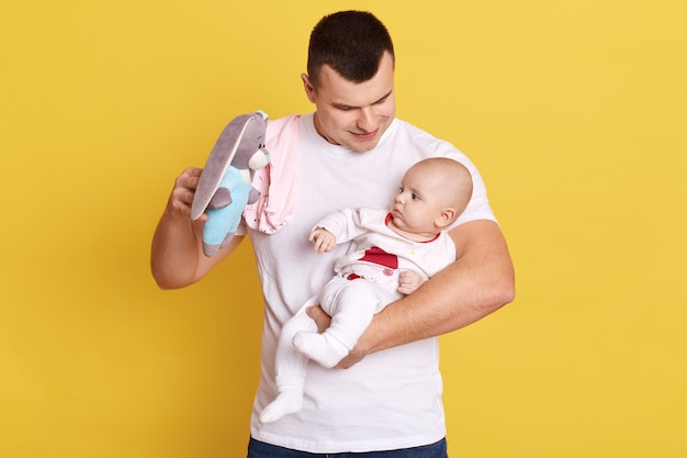 Retrato de padre joven sosteniendo a su bebé recién nacido en manos