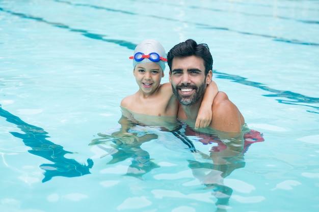 Retrato de padre y niño jugando en la piscina