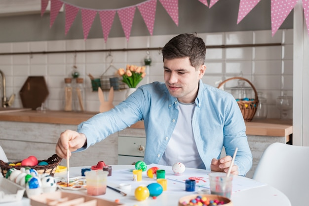 Retrato de padre pintando huevos para pascua