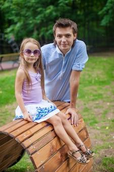 Retrato de padre con su hija sentada en la cama de tablones de madera en el parque