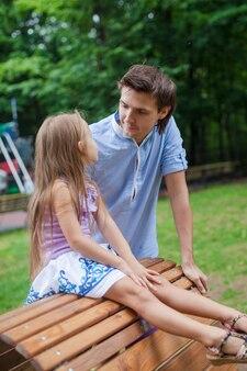 Retrato de padre con su hija sentada en la silla de madera