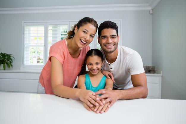 Retrato de padres e hija de pie juntos en la cocina