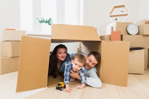 Retrato de unos padres felices jugando con un niño pequeño dentro de la caja de cartón