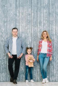 Retrato de los padres de pie con su hija sosteniendo osito de peluche contra el fondo de madera
