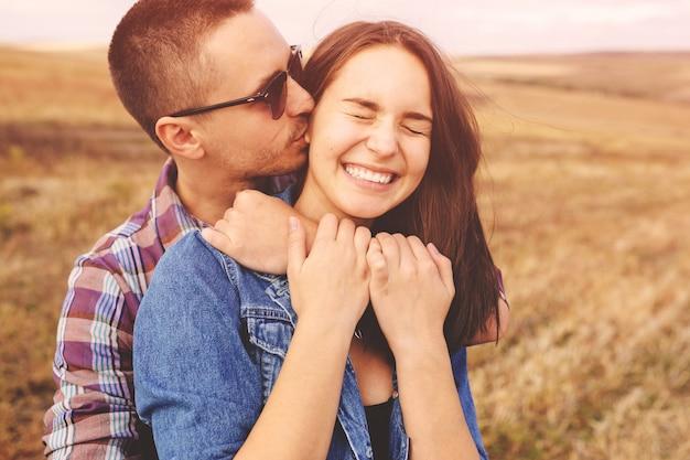 Retrato del paisaje de la joven pareja elegante hermosa sensual y divirtiéndose al aire libre