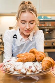 Retrato de un panadero femenino feliz que toma los olores del croissant cocido en él soporte de pastel de vidrio
