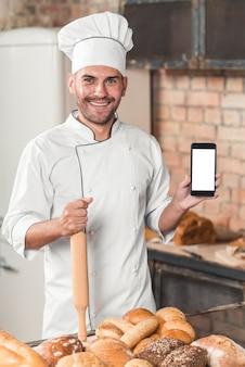 Retrato del panadero de sexo masculino que muestra el teléfono móvil en blanco con panes cocidos