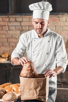 Retrato del panadero de sexo masculino que sostiene la barra de pan de la bolsa de papel