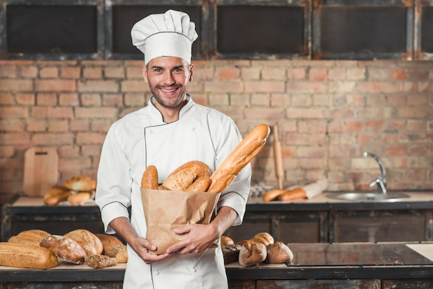 Retrato del panadero de sexo masculino que sostiene el pan de panes en bolsa de papel
