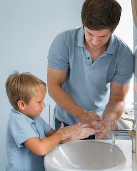 Retrato de papá enseñando a su hijo a lavarse las manos
