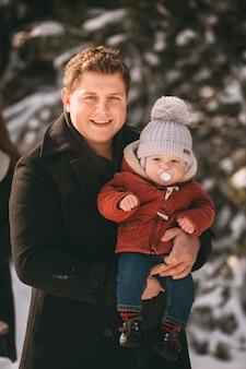 Retrato de papá con hijo en bosque de invierno. la familia pasa un buen rato juntos