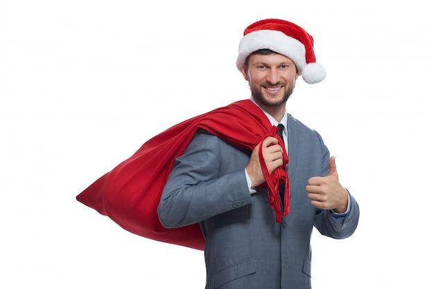 Retrato de papá noel positivo en suite gris, gorra roja y bolsa llena sobre el hombro, sonriendo y mostrando super.