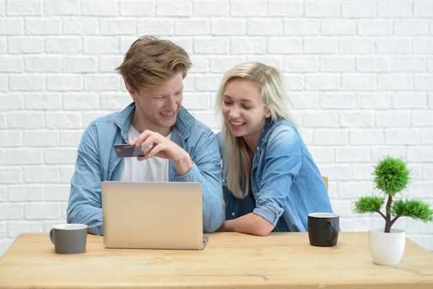 El retrato de un par alegre que hace compras en línea con el ordenador portátil mientras que se sienta en la tabla en casa, los hombres que sostienen la tarjeta de crédito y goza.
