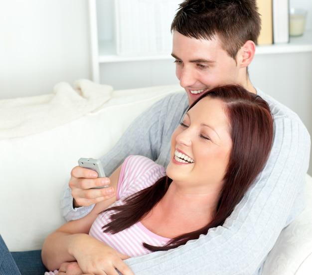 Retrato de una pareja abrazándose viendo la televisión tumbada en el sofá