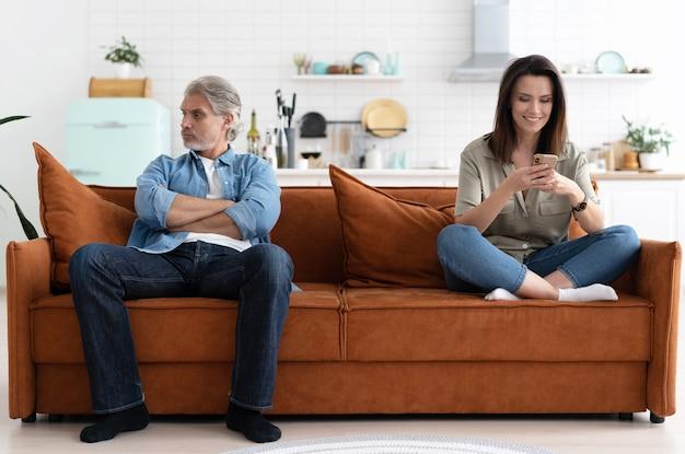 Retrato de una pareja adulta media sentada en el sofá después de la pelea.