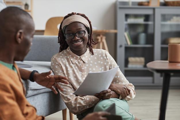 Retrato de una pareja afroamericana moderna que trabaja desde casa juntos, se centran en la mujer joven sonriente que sostiene el documento mientras está sentado en el piso, espacio de copia