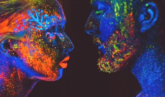 Retrato de una pareja de amantes pintados en polvo fluorescente.