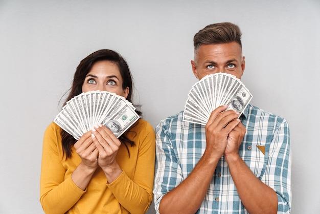 Retrato de pareja amorosa adulta emocional sosteniendo dinero aislado sobre la cara que cubre la pared gris