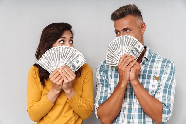 Retrato de pareja amorosa adulta sosteniendo dinero aislado sobre pared gris que cubre la cara mirando el uno al otro