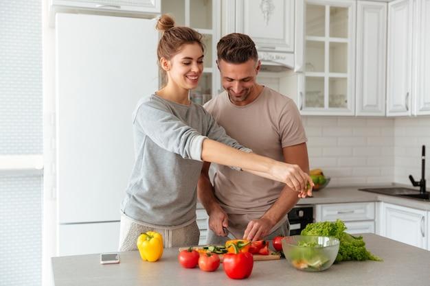 Retrato de una pareja amorosa alegre cocinar ensalada juntos